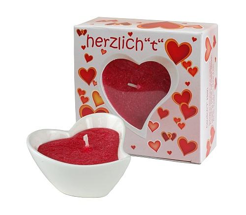 Geschenke, die von Herzen kommen. Schale in Herzform aus weißem Porzellan, gefüllt mit rotem Stearin.